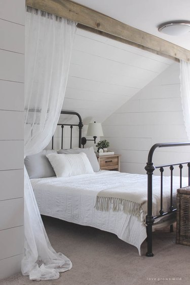 lace curtains hanging from wood beam in bedroom