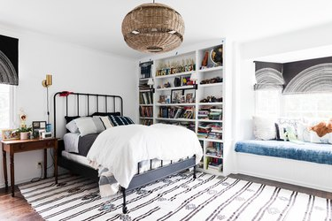 bedroom idea with iron bed frame and floor to ceiling built-in bookcase next to window seat