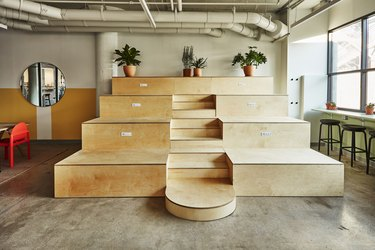 photo of wooden bleachers with planters on top and a round mirror to the left
