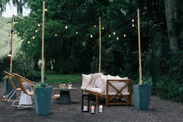 modern outdoor party idea with seating area and string lights and lanterns