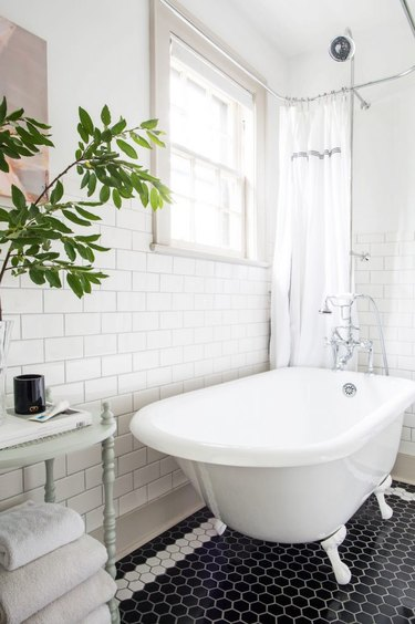 white bathroom with white subway tile walls and black and white hexagon mosaic floor tile