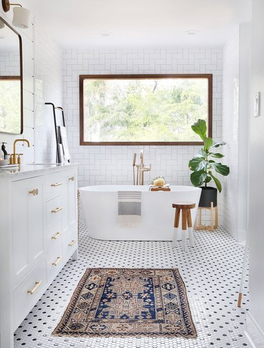 Bathroom fiddle leaf fig near freestanding bathtub and large window