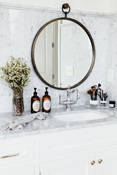 white bathroom with marble countertop and backsplash with round framed mirror