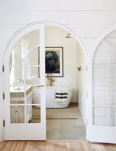 white farmhouse bathroom with freestanding bathtub and black and white artwork