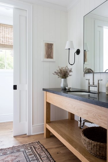 bathroom with wood vanity and black countertop