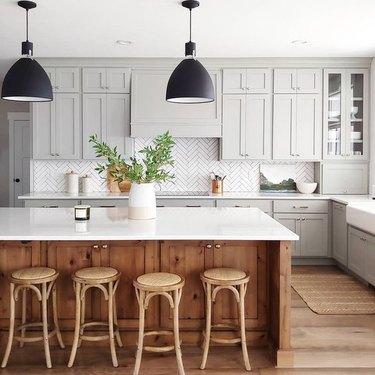 gray kitchen color idea with wood island and herringbone tile backsplash