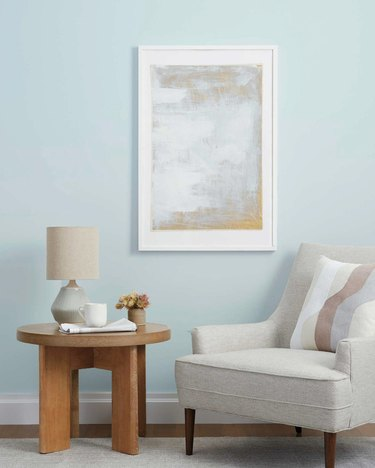 gray chair with wood table and framed artwork on the wall
