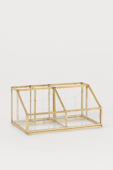 glass bathroom countertop storage with brass trim