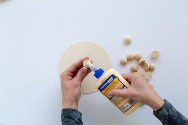 Applying wood split beads to a wood circle using wood glue.