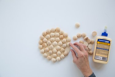 Adding split wood beads to a wood circle using glue to make a modern trivet.