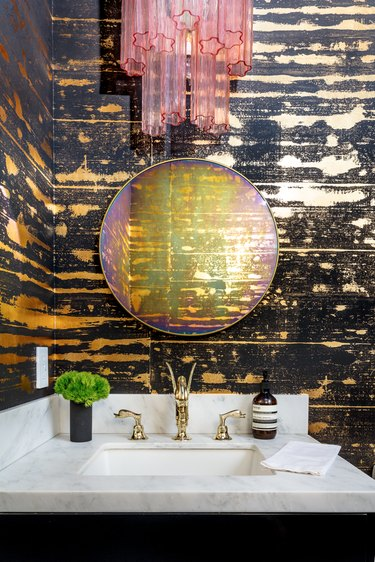bathroom with textured wall, pink lighting fixture, and marble backsplash