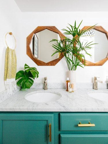 bathroom space with bright cabinets and two wooden mirrors