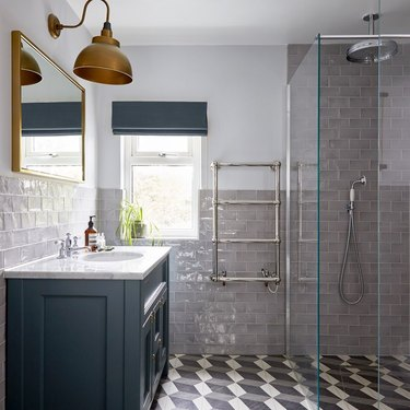 modern shower idea with patterned floor tile and blue cabinets and brass sconces