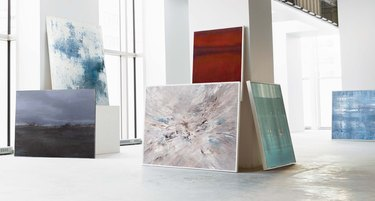 White gallery space with large abstract paintings leaned against walls