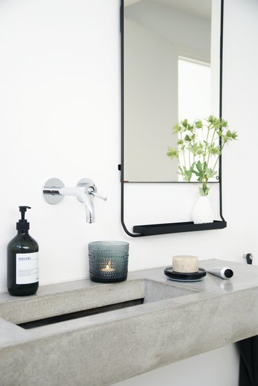 minimalist bathroom with luxe accessories on concrete countertop