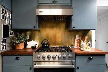 stainless steel gas range and vent hood, blue cabinets, smoke-effect backsplash