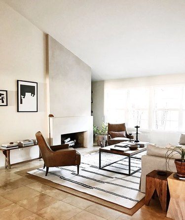modern living room with concrete fireplace and angled ceiling