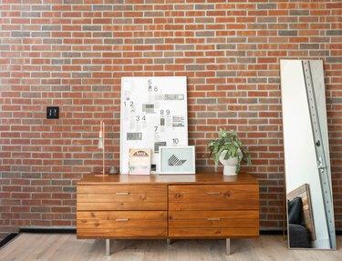 credenza in front of brick wall, mirror, artwork