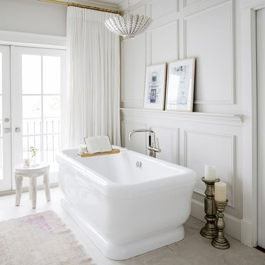 all white bathroom with freestanding tub and floor-to-ceiling drapery