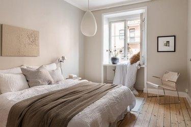 Scandinavian inspired beige bedroom with wood flooring and white trim