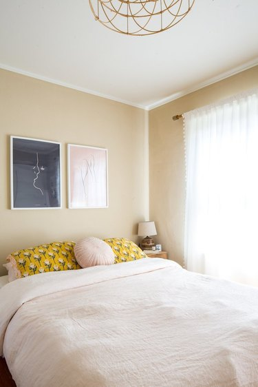 beige bedroom with yellow throw pillows and white drapery