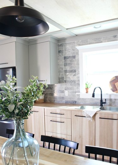 Scandinavian chic kitchen with light wood cabinets and double sink