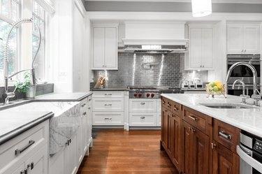 white kitchen with dark wood cabinets and metal subway tile backsplash