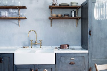 blue farmhouse kitchen with open shelving and double sink with gooseneck faucet