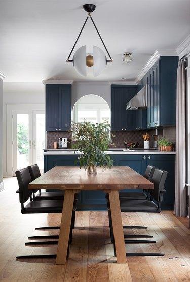 dark blue kitchen cabinets with bronze mosaic tile backsplash