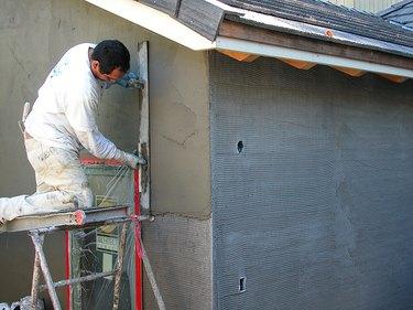 Workman troweling stucco.