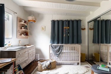 nursery space with wooden dresser, crib and dark blue curtain