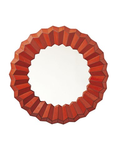 Circular wall mirror with thick orange-red wavy border
