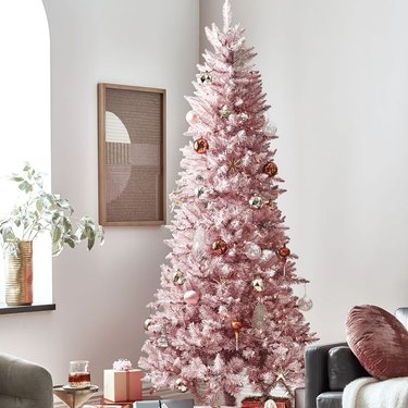 Christmas Tree Themes with Pink artificial Christmas tree, art on wall, purple throw cushion.
