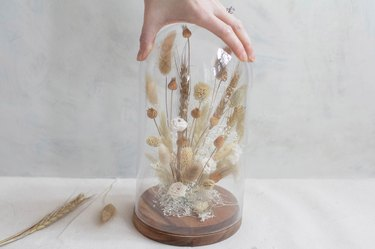Placing cloche over dried florals