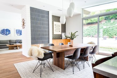 Midcentury modern style dining room with black Eames chairs and tile accent wall