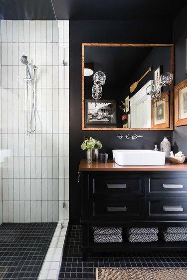 black bathroom with wood countertop