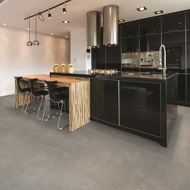 kitchen space with black cabinets and gray cork flooring