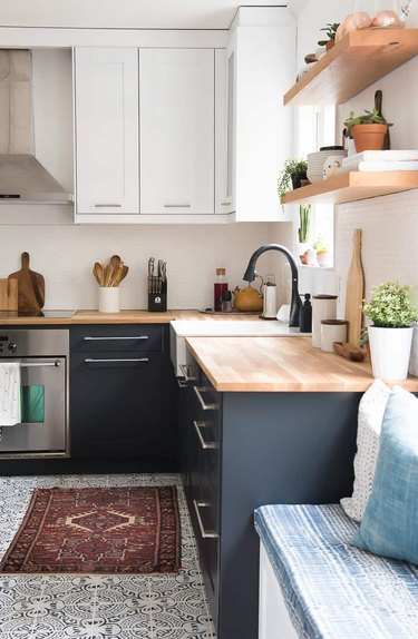 two-tone kitchen cabinets with white and navy blue and patterned floor tile and butcher block countertops