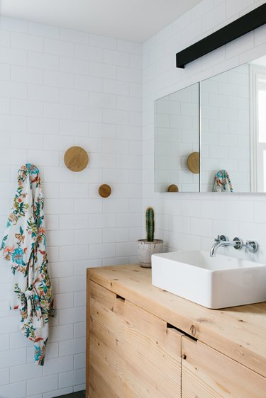 wood vanity cabinet with vessel sink and white subway tile