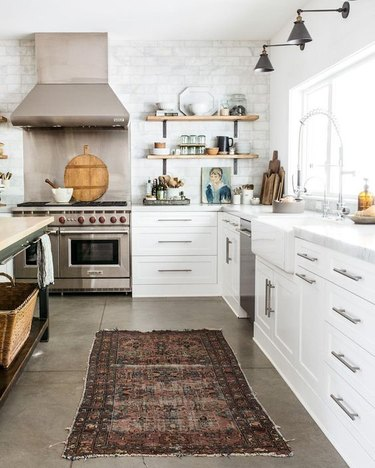 modern kitchen with concrete flooring topped with runner