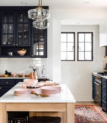 pink kitchen color idea with timeless pink dishware and dark blue cabinets
