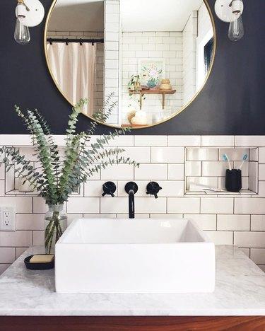 bathroom backsplash idea with white subway tile behind vessel sink on marble countertop