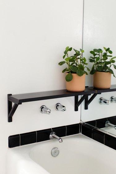 bathroom backsplash idea with black subway tile around white bathtub
