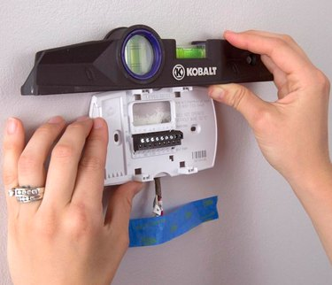 Programmable thermostat being installed.