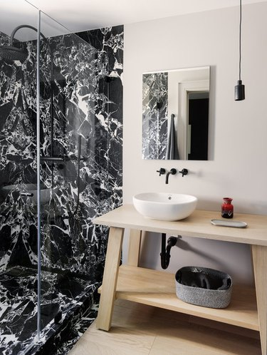 modern black and white bathroom with wood countertop and vanity