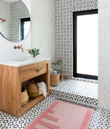 Minimal bathroom with floor-to-ceiling black and white tile, blush geometric rug, and wooden minimal vanity