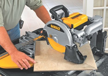 Cutting tile with a saw.