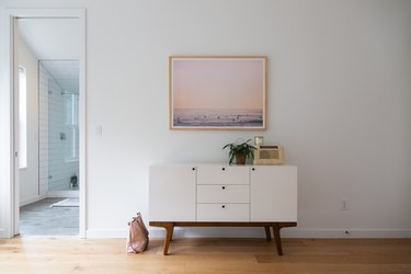 focus on credenza with white walls, wood floors