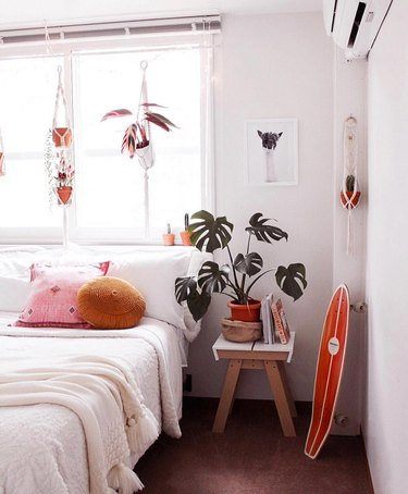 white bedroom with pops of orange decor