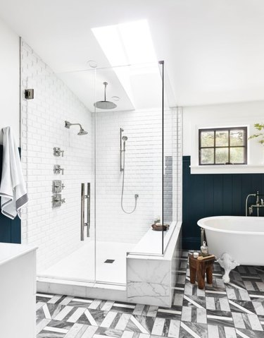 Grey and white geometric floor tile and white tiled shower in bathroom designed by Emily Henderson.